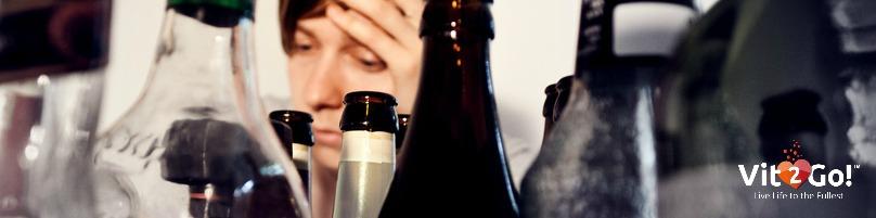 Junger Mann inmitten vieler Flaschen Alkohol