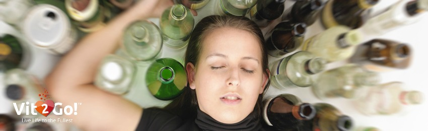 Young, partially drunk woman surrounded by bottles